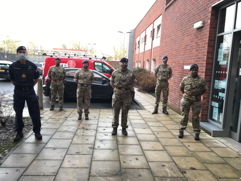 5 army personnel wearing masks standing outside the medical practice